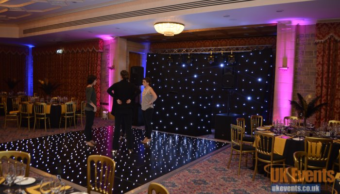 A black starlit dance floor with uplighters and star cloth backdrop for a birthday party