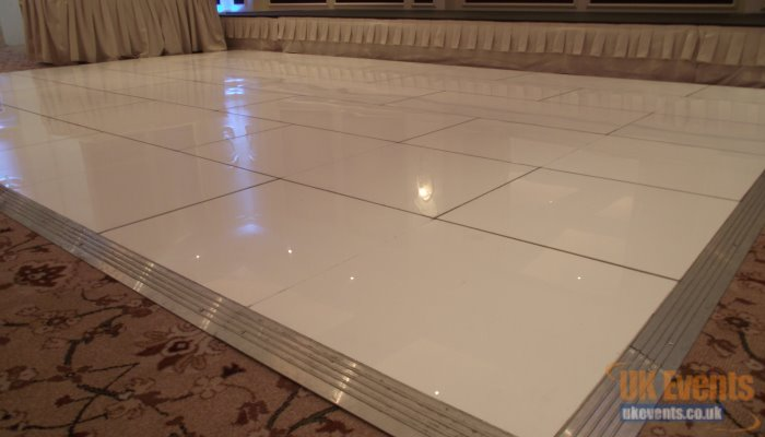 a plain white dance floor that was installed to a marquee