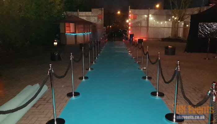 Green carpet with ropes and posts installed outside
